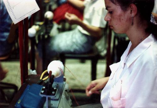 Worker sewing Rawlings baseball