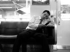 Osaka Salaryman (joyjwaller) Tags: portrait blackandwhite broken japan train phone tie dude suit transit hawt osaka exhausted salaryman bruised walkbyshooting huhhuhyeah