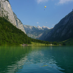 Enjoying his airy cocpit view above lake Knigssee (Bn) Tags: lake germany deutschland bavaria berchtesgaden topf50 kings fjord hikers paragliding thealps soaring topf100 bluelake topf200 paragliders verticalpanorama knigssee stbartholom 100faves 50faves 200faves bayerischealpen nationalparkberchtesgaden jennerbahn berchtesgadennationalpark germanbavarianalps southofgermany schnauamknigssee berchtesgadenalps cleanestlakeingermany stretchesabout77km formedbyglaciers nearborderwithaustria jennermountaintop1870m picturesquesetting sheerrockwalls playaflugelhorn steeplyrisingflanksofmountainsupto2700m hikingtrailsupthesurroundingmountains royalmountainexperience paraglidingoverthebavarianalps saletmoraine