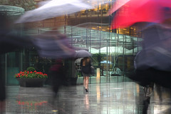Under My Umbrella, Broadgate Circus (flatworldsedge) Tags: city red blur london wet water girl rain reflections workers legs gorgeous broadgate rainy commute granite cropped umbrellas cityoflondon gaucho shortskirt broadgatecircus improvisedtripod gerania shutterdelay turquoiseglass yahoo:yourpictures=weather yahoo:yourpictures=waterv2