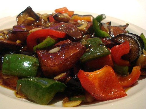 Deep-fried pieces of potato and aubergine are piled on a platter with pieces of red and green pepper, coated in a shiny brown sauce.