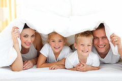 Young family playing together on a bed (Lensation Studio) Tags: adult affection beautiful bed bedroom boy caucasian child concept cuddling dad day down embracing family father female fun girl happy having home horizontal hugging indoors kids lady laughing life lifestyle love lying man mom morning mother mum parent people play playful portrait relaxing smile smiling togetherness white woman young