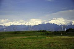 White electricity towers in front of mountains (Horia Varlan) Tags: sky mountains green field lines clouds landscape evening moving metallic horizon towers powerlines romania electricity peaks distance snowcovered fagarasmountains