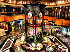 Elegant Lobby (` Toshio ') Tags: city travel flowers light people woman man building clock architecture night reflections asian carpet hotel chair singapore asia cityscape orchids chairs interior crowd clocktower lobby couch tables elegant magnificent orchardroad orchardhotel toshio