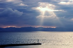 A man and the elements (n.pantazis) Tags: trip blue light summer sky sunlight man weather clouds port dark fisherman waterfront cloudy seawall greece rays beacon beams pentaxkx rafina evia