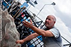 (dcheese.it) Tags: man senior boat fishing fisherman holding 60s cloudy cigar smoking help sailor searching fishingnet