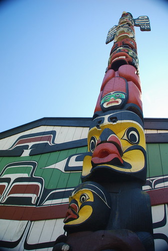 Totem pole in front of big house, Royal BC Museum, Victoria, BC, Canada