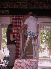 a man sitting on the top of a ladder hanging a curtain with a woman standing handing him a curtain