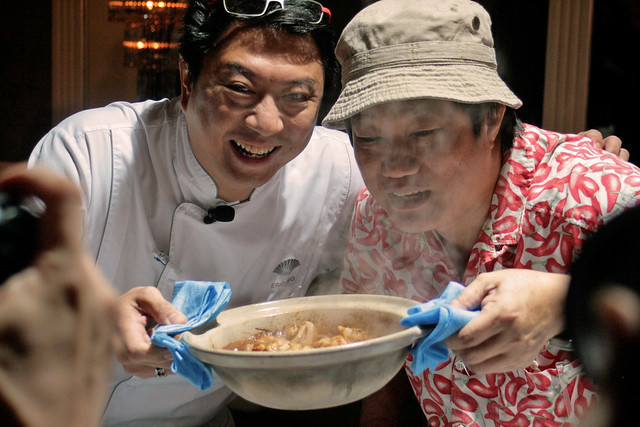 Executive Chef Eric Teo and KF Seetoh holding up the very hot claypot of sesame-ginger chicken