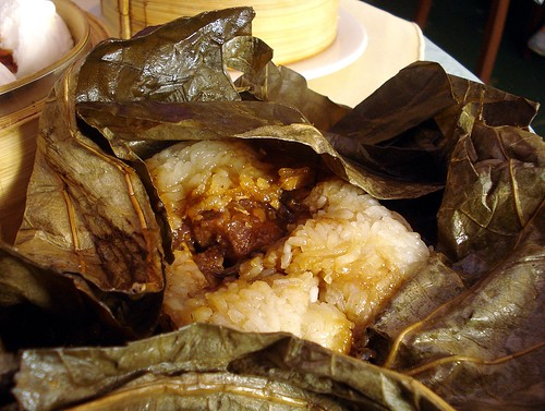 The parcel from above has now been unwrapped, revealing a quantity of steamed glutinous rice with a number of small chunks of bone-in chicken gathered together in its centre.  Some of the sauce from the chicken has soaked into the rice.
