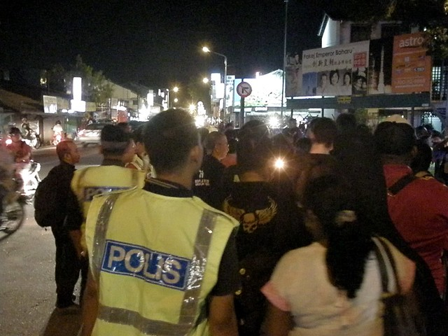 A lone candle burns brightly in the night as police close in on anti-ISA protesters outside the Jelutong Police Station