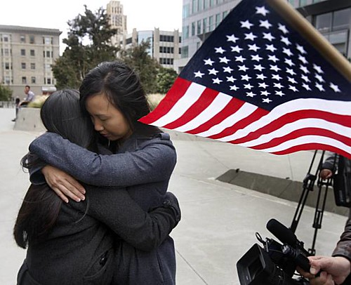 two women embrace fiercely on a city street. An American flag waves in the corner