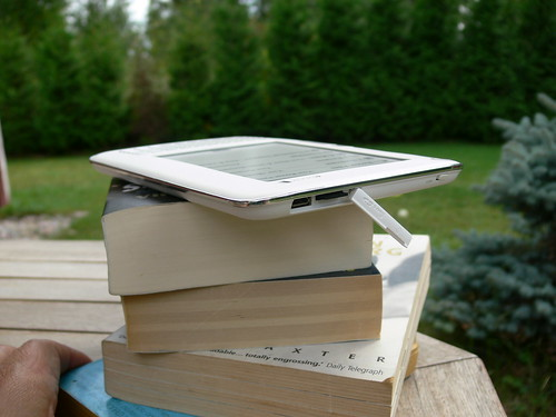E-kirjojen lukulaite ja painettujen kirjojen pino