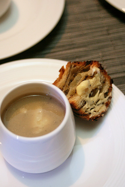 Truffle-artichoke soup with grated parmesan cheese, served with truffle brioche spread with truffle butter