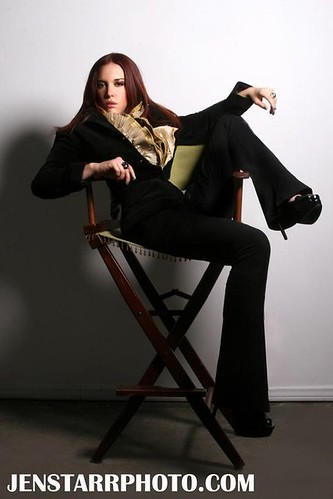 Shannon Lark lounges in a directors chair. She has long red hair and wears black flared pants with spikey heels.