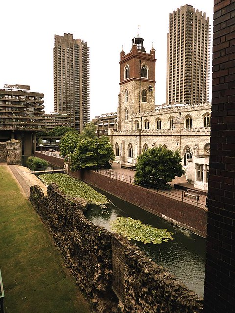 Roman wall, pond, and church flanked by concrete towers