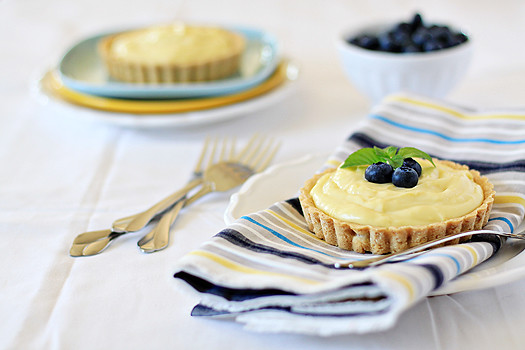 A mini custard tart topped with fresh blueberries, with another tart in the background.