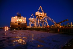laid up ore boat (Studiobaker) Tags: blue winter sunset sky snow cold ice up night reflections screw screws evening harbor boat twilight dock afternoon wind crane dusk spirit shift superior windy crack american late propellers tied cracks load frigid propeller lakers ore duluth prop laker groan laid floe unload cracking shifting americanspirit creak floes winterized icebound studiobaker