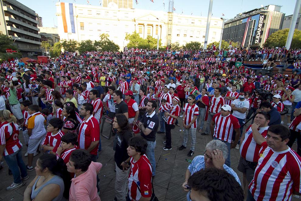 El público observa atento el encuentro de la Albirroja ante el seleccionado de España en la Plaza de la Democracia, vistiendo la casaca de la selección. (Tetsu Espósito, Asunción, Paraguay)