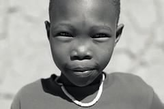The Look (Miss Kels) Tags: africa boy portrait people blackandwhite bw playing film face closeup kids canon kid eyes san play close desert documentary posing environmental 7d stare botswana plains filming kalahari indigenous