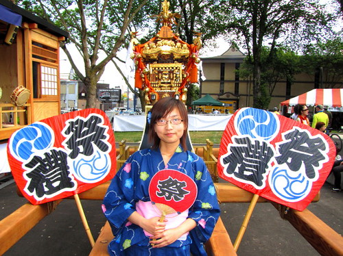 Young lady dressed in Kimono pose before Omikoshi portable Shinto shrine, Powell Street Festival 2010 where Japanese tradition meets new expression in Vancouver Canada
