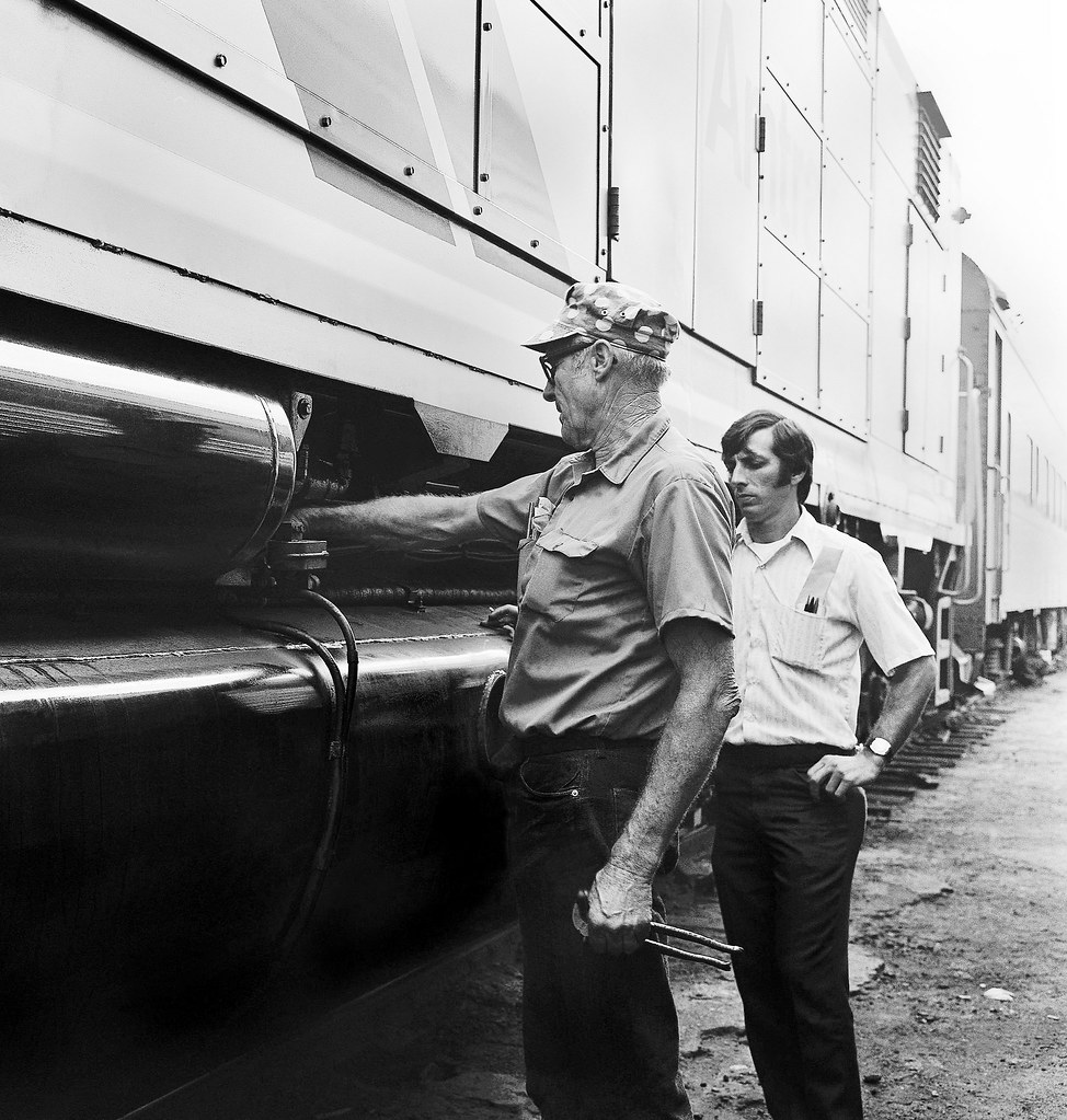 Amtrak EMD SDP40F is being maintained and serviced by SCL Railroad Electrician Charlie Bruorton, as shop foreman Joe looks on at the SCL (former ACL) railroad yard in Saint Petersburg, Florida, 1975