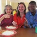 Volunteer Julie Allen, Jennifer Campbell, and Kenny Hau share a delicious lunch of nshima and cabbage.
