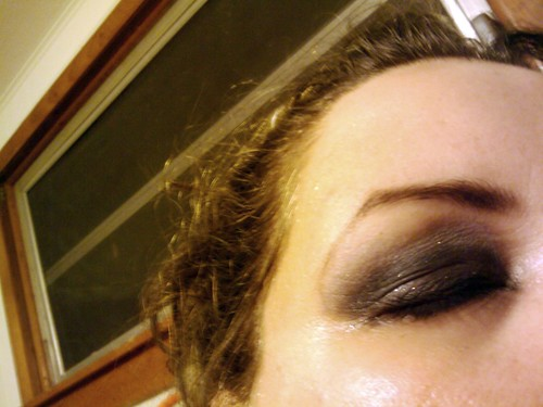 Closed eye, eyeshadow in shades of black and silver, very smoky