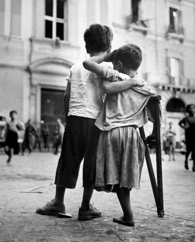 Children in Naples, Italy, little boy helps one-legged companion across street, the boy lost his leg as a result of the war, Aug 1944, by Wayne Miller