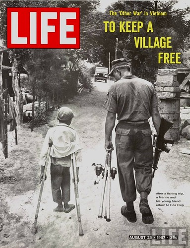 After a fishing trip, a Marine and his young friend on crutches return to Hoa Hiep, Vietnam, by Co Rentmeester 1967
