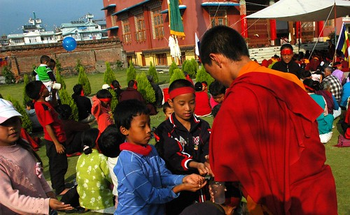 Tibetan children being given nectar from the Hevajra initiation by a monk, Tharlam Monastery courtyard, Boudha, Kathmandu, Nepal by Wonderlane