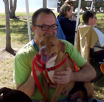 Man holding a pit bull puppy from the Sula Foundation
