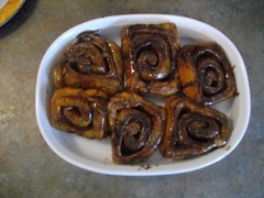 Cinnamon buns are flipped to reveal their glazy goodness