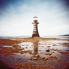 Whiteford Point Lighthouse #5 (slimmer_jimmer) Tags: sky lighthouse reflection beach southwales coast seaside xpro crossprocessed rocks coastal crossprocessing barnacles gower lowtide mussels tidal holga120s kodakektachromee100g e100g whitefordsands whitefordpoint whitefordpointlighthouse