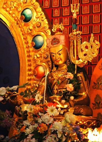 Statue of Guru Rinpoche, Padmasambhava, holding a vajra and nectar skullcup, vajrakatang staff, lotus hat, flowers, colored jewels, Sakya Monastery of Tibetan Buddhism, Seattle, Washington, USA by Wonderlane