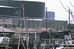 More low-res urban wasteland fun! Shacks and their hand-cobbled wood plank walkways and patios at the Greene Street Boat Club with giant looming oil tanks at the Portside Terminal on the edge of the Morris Canal. Jersey City. April 1976 (wavz13) Tags: oldphotographs oldphotos 1970sphotographs 1970sphotos oldphotography 1970sphotography vintagephotographs vintagephotos vintagephotography filmphotos filmphotography oldbuildings abandonedbuildings industrial industrialphotos industrialphotography secretplaces hiddenplaces forgottenplaces depressing bleak noir noire dark vintagebuildings vintagemovies oldmovies classicmovies vintagefilms oldfilms jerseycityphotographs jerseycityphotos oldjerseycityphotography oldjerseycityphotos oldjerseycity vintagejerseycity vintagejerseycityphotography jerseycityhistory super8movies super8film urbanphotography urbanphotos urbanscenes cityphotography cityphotos cityscenes newjerseyphotographs newjerseyphotos oldnewjersey vintagenewjersey newjerseyhistory vintageindustry oldindustry vintageindustrial oldindustrial industrialjerseycity industrialruins factoryruins industrialwasteland urbanwasteland urbandecay urbanblight urban urbanexploration abandoned jerseycityfactories gloomy grain grainy odd surreal weird postindustrial