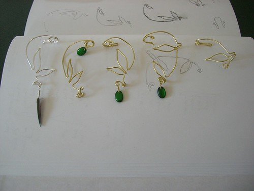 Ear cuffs in a row. Silver with feather; brass with beads (and without).