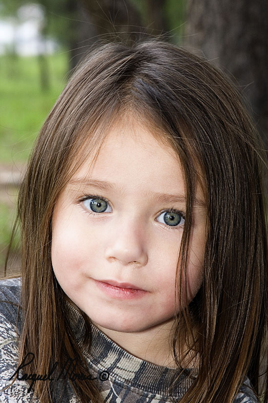 Little girl with curly brown hair and blue eyes