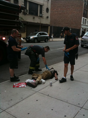 EMTs assisting man lying on the ground