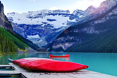 Red Canoes (Jim Boud) Tags: travel blue red mountain lake canada mountains reflection green nature water pinetree canon lens landscape outdoors eos gold boat is nationalpark colorful paradise peace hill smooth relaxing rocky floating peaceful wideangle canadian canoe shore alberta valley boating northamerica banff usm canoeing dslr lakelouise 1785mm digitalrebel relaxed photoart digitalslr pinetrees efs1785mmf456isusm province firtree waterscape artisticphotography canadianrockies imagestabilization imagestabilized 550d jimboud t2i photomatixhdr exposurefusion jamesboud eos550d kissx4