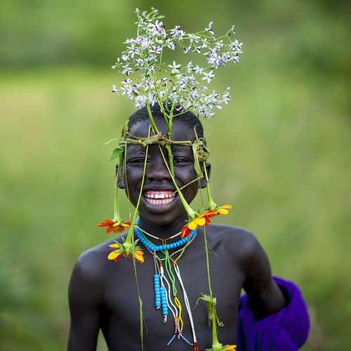 Surma tribe kid with flowers decoration - Omo Ethiopia by Eric Lafforgue