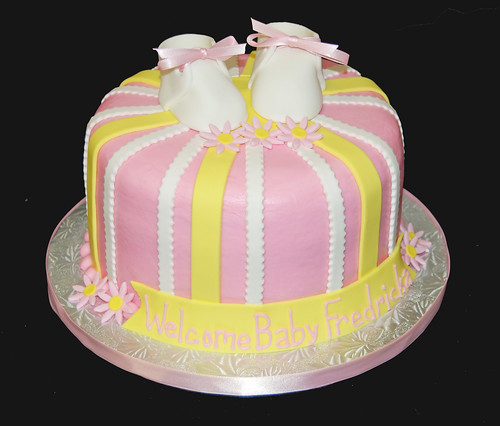pink and yellow striped baby shower cake wiht booties and daisies