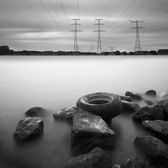 Silent witness (Dutch Dennis) Tags: longexposure sky bw industry water netherlands monochrome car clouds river rocks long exposure industrial power stones parts surreal blurred pylon filter pollution electricity locks heel waste pylons tyre limburg niederlande longexposurephotography nd110 1dmarkiii dutchdennis