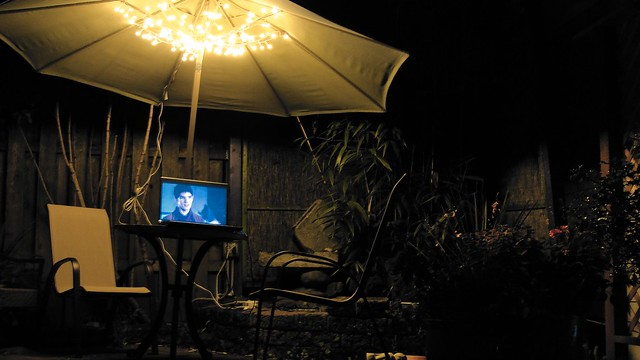 Photo of my back yard at night, with umbrella table, fairy lights, and my laptop showing an episode of Merlin.