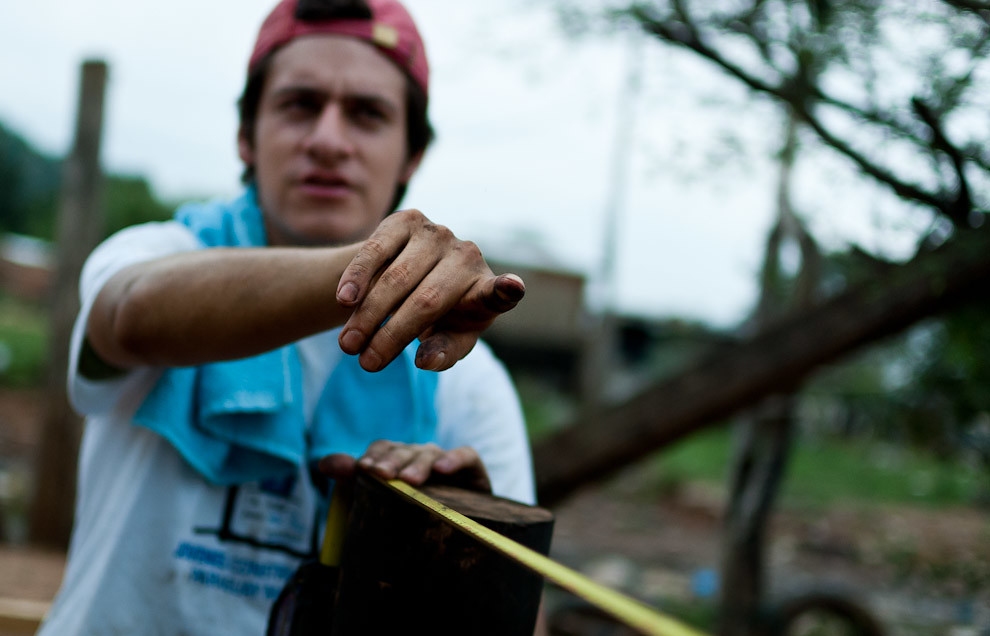 Voluntario lider de cuadrilla da las orientaciones para medir la distancia de los pilotes en la etapa de instalación de los cimientos de madera. (Elton Núñez - Asunción, Paraguay)