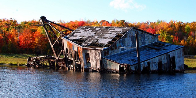The half-sunken Quincy No. 2 dredge with fall colors and reflections.