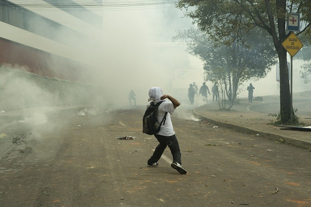 Demonstrator throwing rock towards troops
