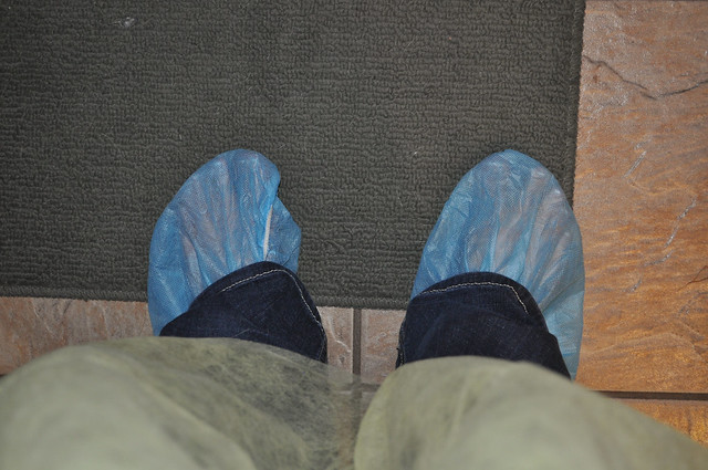 a picture of my feet with blue sterile disposable booties like ones you might find in hospitals, they are kind of see through so you can kind of see my toes.