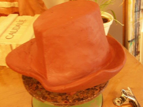 Sculpture en terre figurative représentant un chapeau dont les bords sont légèrement relevés et destiné à coiffer un gardien assis – Sandrine Vallée