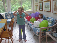 Speck sitting in a heap of balloons, while cousin S demonstrates a wiggly critter